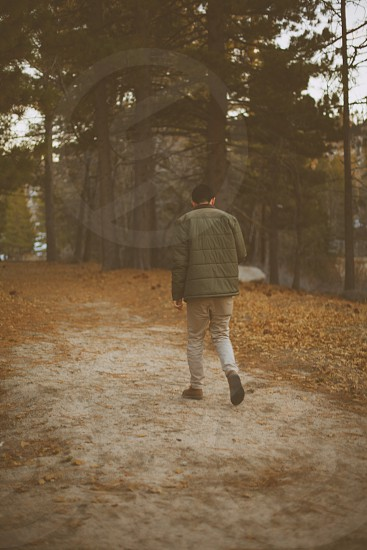 man wearing a black coat walking on a dirt path photo