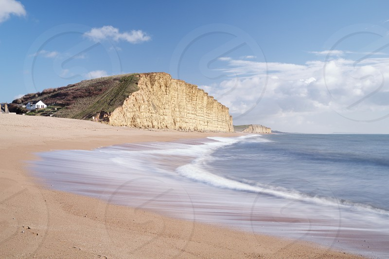 A beautiful day lights up the huge cliffs of West Bay Devon UK. photo