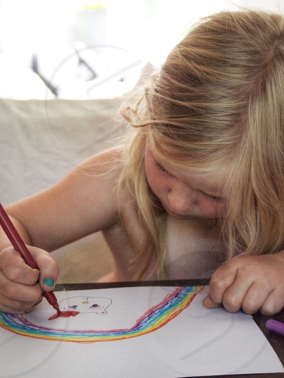 Girl kid child painting drawing rainbow colours focus concentrated Sweden  photo