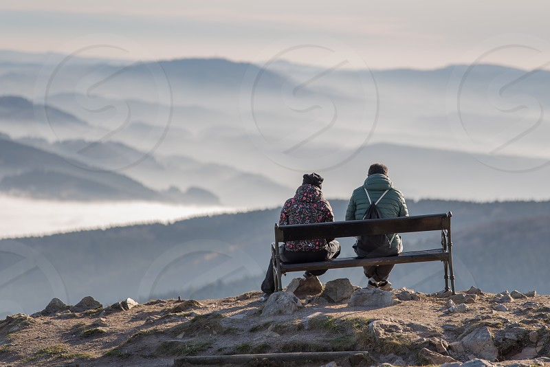Two young people sitting on a bench at the prospect of sunrise photo