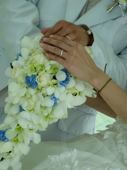 man and woman holding bouquet of white flower photo