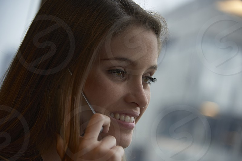 Beautiful young woman in the office on her mobile phone talking to a client photo