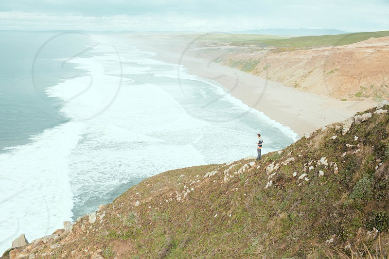 man standing on cliff with ocean view photo