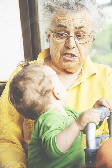 Grandmother having fun and making faces with her baby grandchild. photo