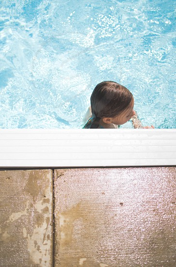 Child in a pool swimming.  photo