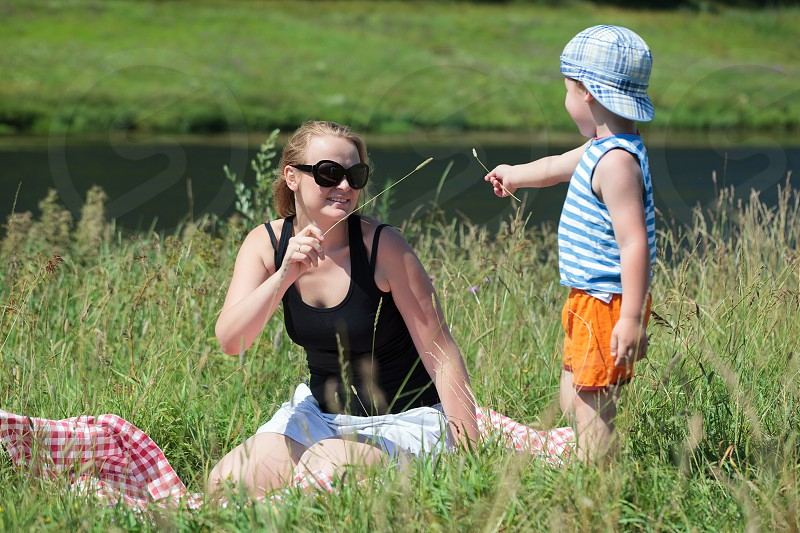 Happy mother and little son playing with grass on the meadow on the bank of a small river. Family fun outdoor photo