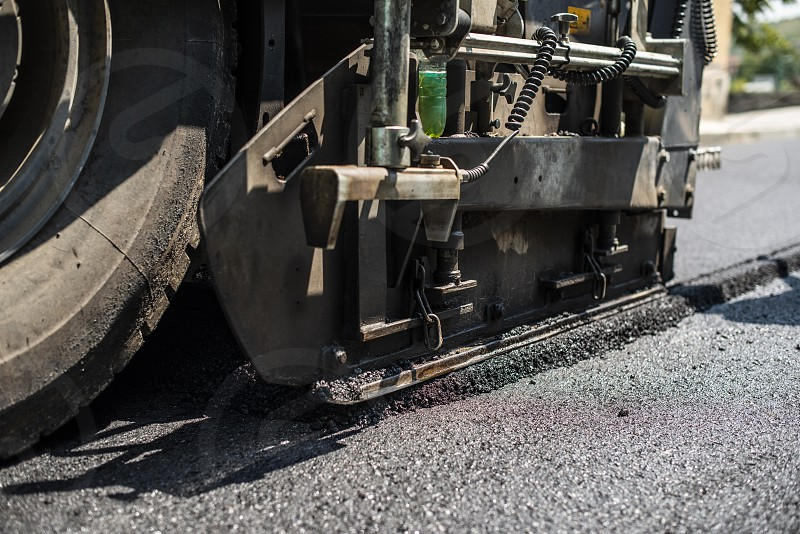 Asphalting machine on the road. Close up photo