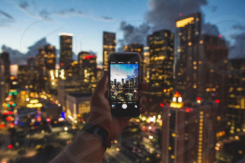 person taking photo of city night photo