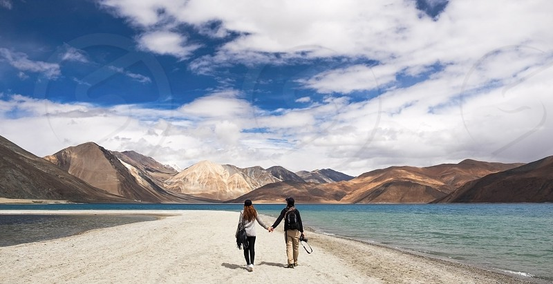 Couple hold hand walking together on the sand be side lake photo