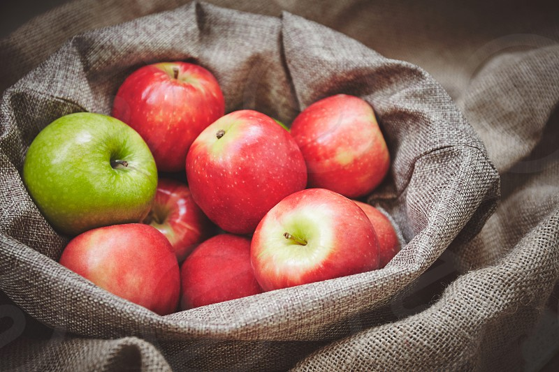 Harvest time in fall Red apple and green apple in basket with burlap background texture Organic fresh apples side view in close-up photo