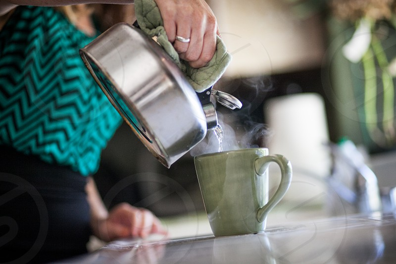 A woman pours hot water from a kettle to a teacup. photo