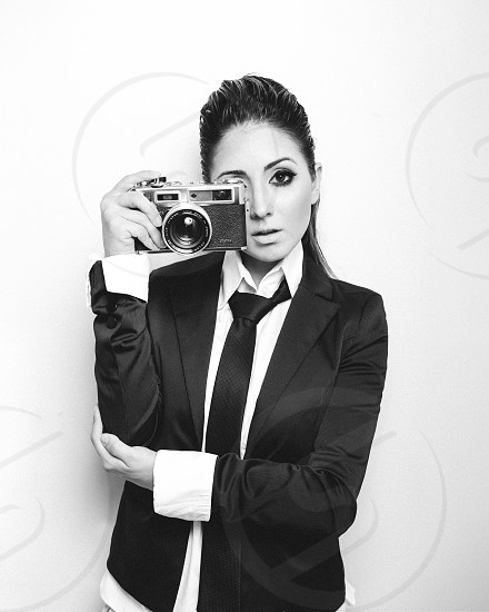grayscale photo of woman wearing suit holding a camera photo