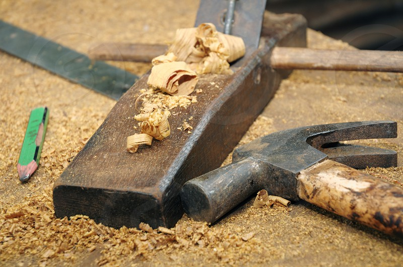 Closeup of carpentry tools on wooden table. Wood planer hammer pencil. photo