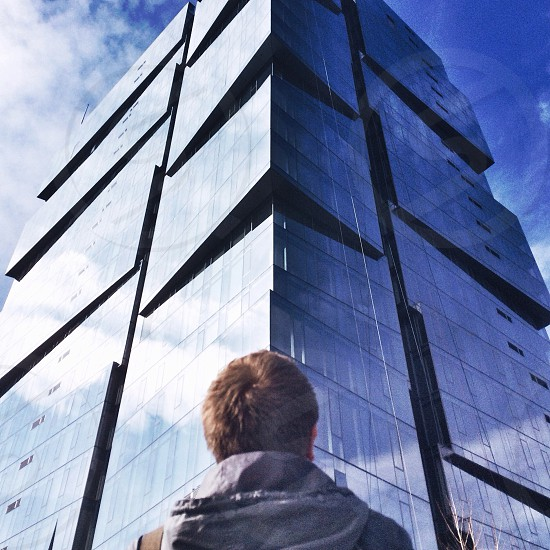 man standing looking up on high rise building photo