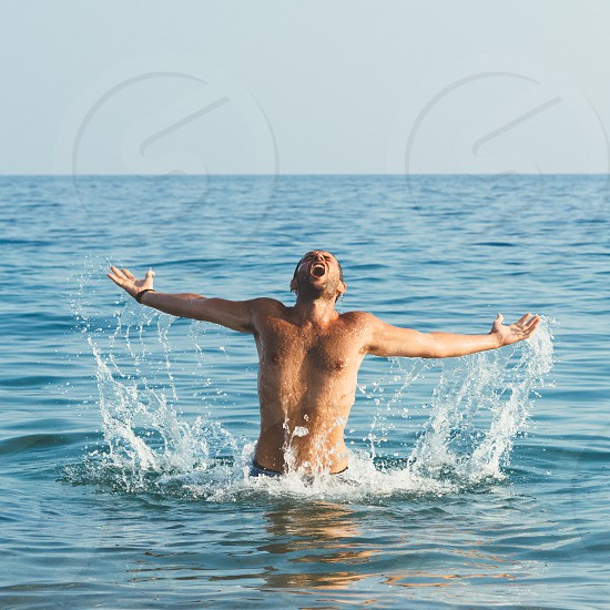 Handsome muscular guy jumping from water photo