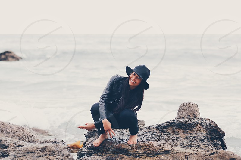 smiling woman in black leather jacket squatting on rock at beach shore during daytime photo