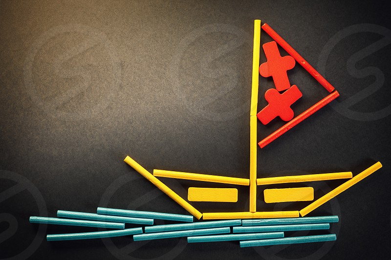 Funny composition presents lonely boat on sea made of wooden sticks in various colors.  photo