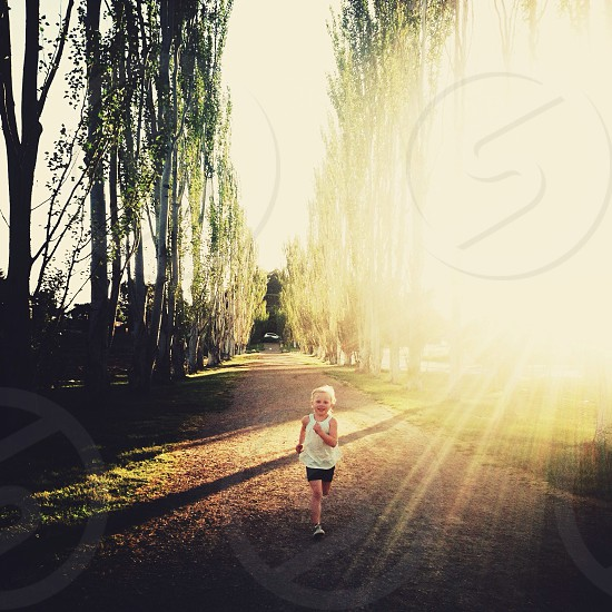 girl in white tank top and black shorts smiling and running down tree lined path photo