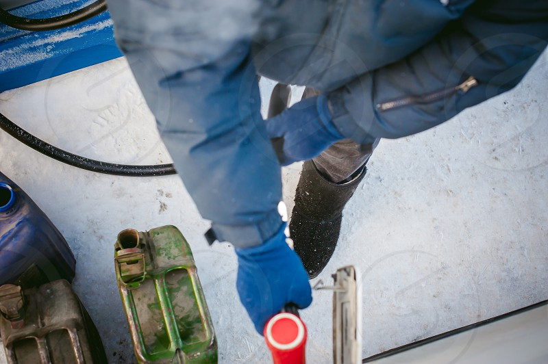 adult man fills a car with petrol at a fuel station in the winter. refueling nozzle man holding in his hand pouring the liquid in the canister and fuel tank photo