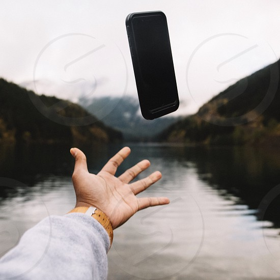 black smartphone in mid air above left hand photo
