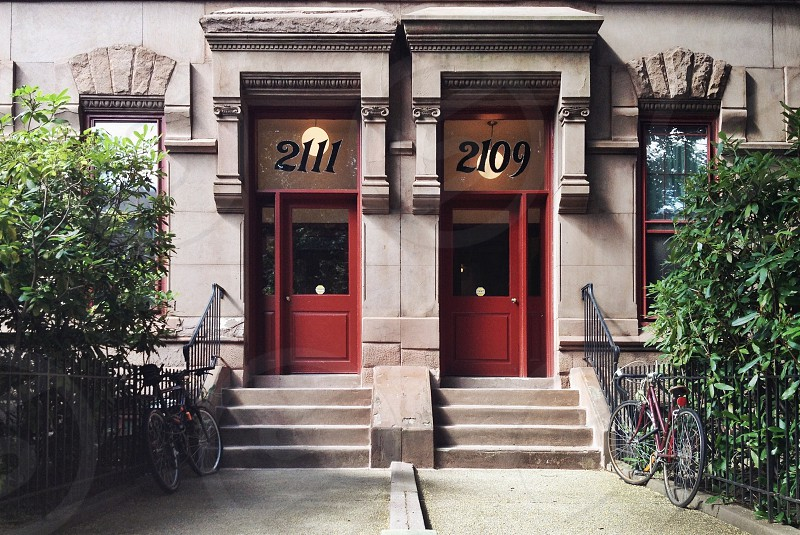 House door red bikes steps architecture detail stone facade city urban numbers photo