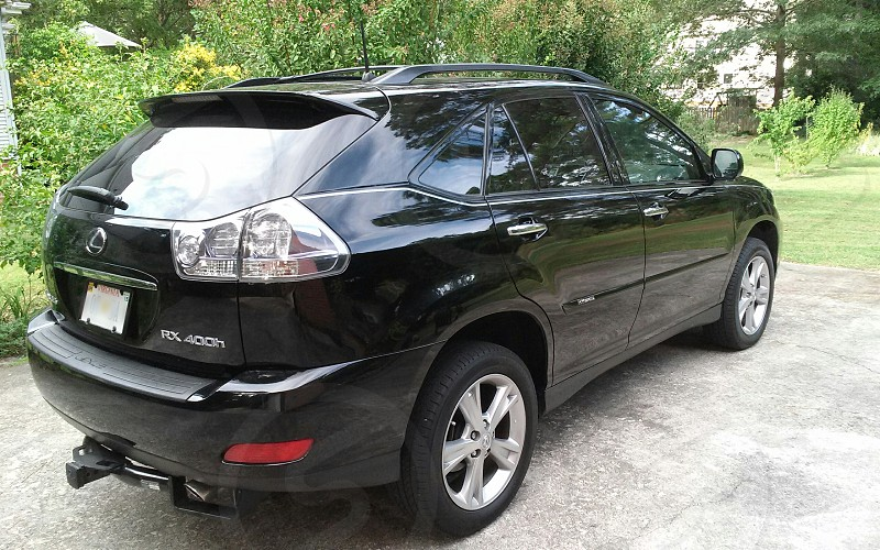 black lexus rx 400 suv parked in driveway near green trees photo
