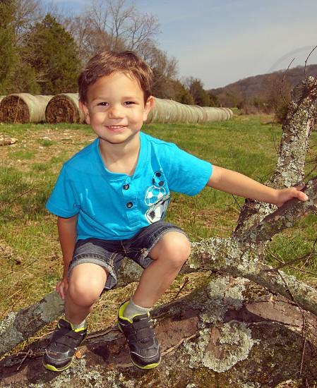 boy in blue shirt holding branch in field photo