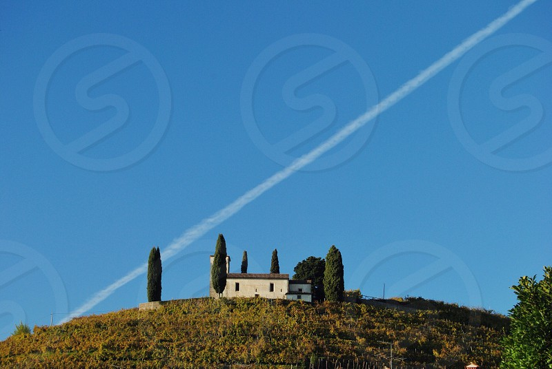 white villa on a vineyard hillside with trees under a white jetstream in a blue sky photo