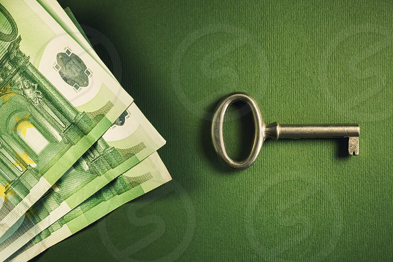 Euro one hundred banknotes and metal key symbolically presenting success.  photo
