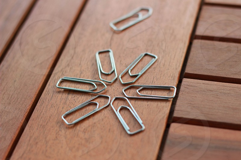 7 grey steel  paper clips on photo