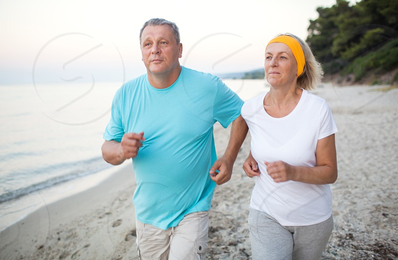 Senior man and woman having a run along the shore. Scene with sea sand and trees. Healthy and active way of life photo