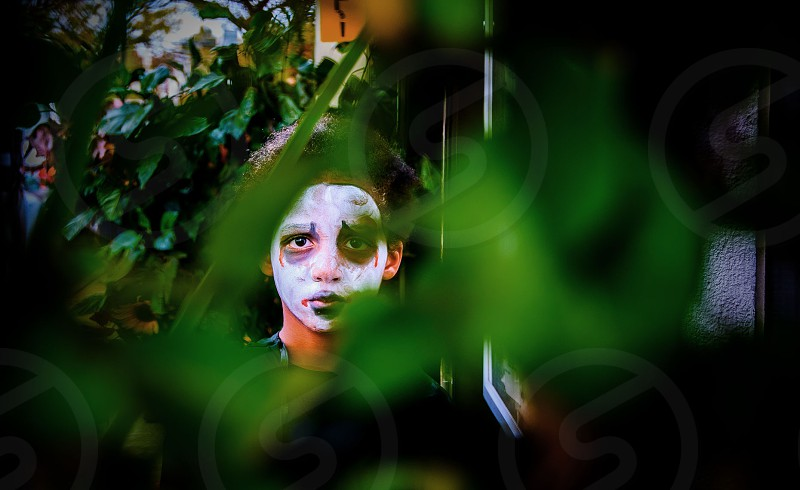boy wearing white skeleton face paint behind green leaves w photo