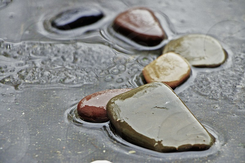 flat faced stones on watery sand photo