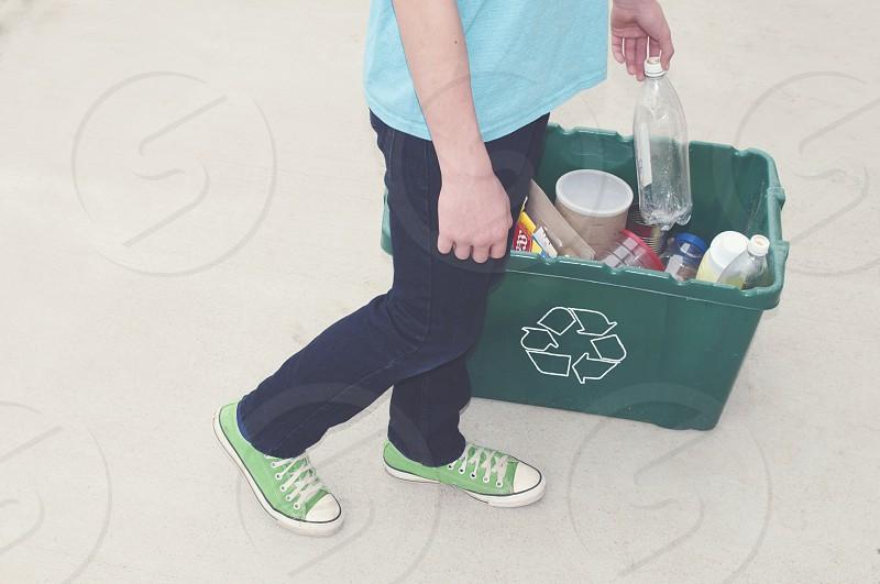 person in black pants standing beside green recyclable trash bin photo