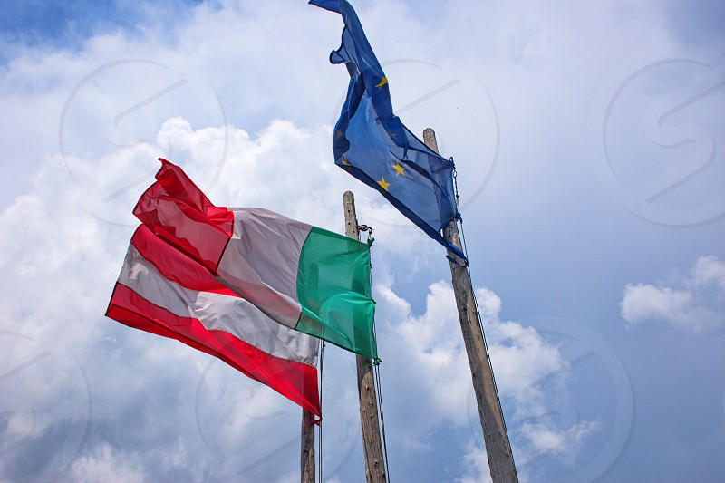 low angle view of flags of Italy Austria and European Union in Brenta Dolomites Italy photo