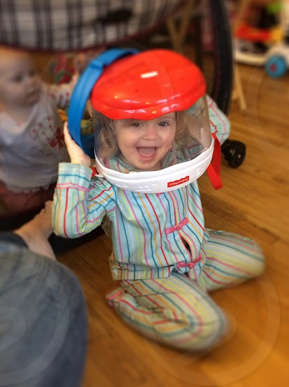 girl wearing blue red and yellow long sleeved pajama set smiling with a clear bucket over her head photo