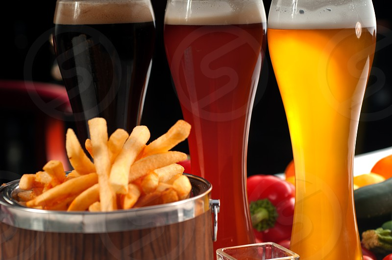 fresh french fries on a wood bucket with selection of beers and fresh vegetables on background photo