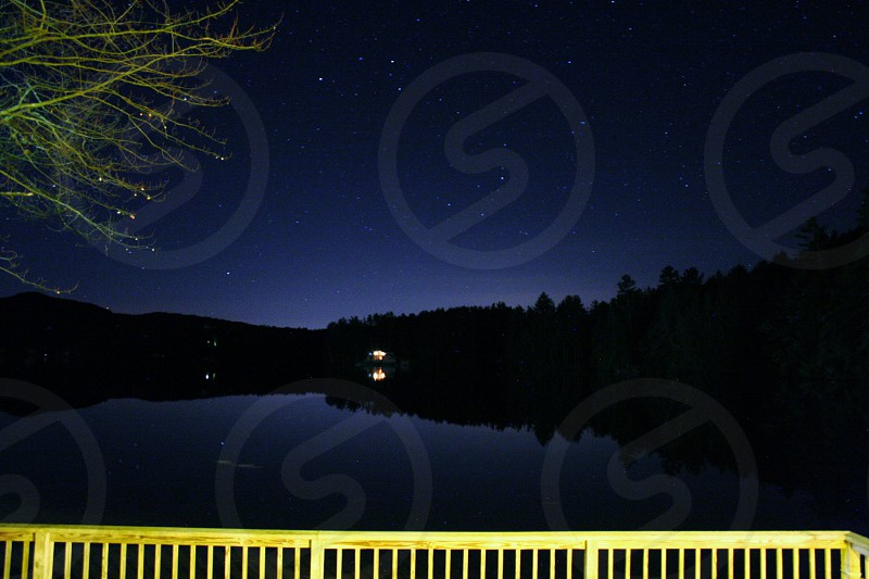 Adirondack lake reflecting at night with stars.  photo