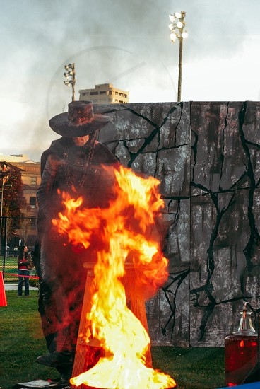Fire performance rock wall dusk spooky hat fedora explosion one person hidden face circus dark scary. Anonymous fireplace  photo