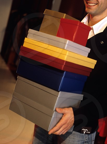 A man carrying a stack of boxes in a clothing store and smiling photo