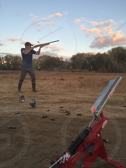 man wearing black t-shirt and holding rifle while playing clay target photo