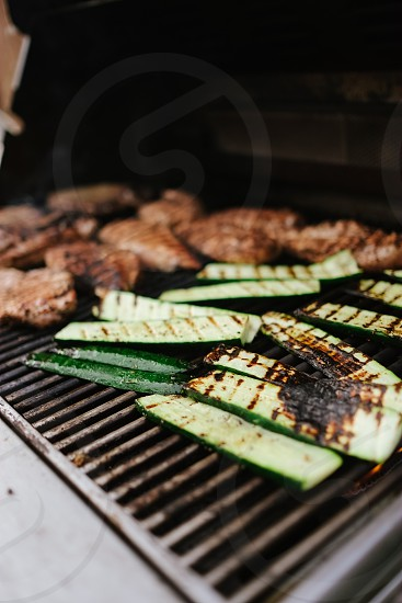 grill cucumber and meat on black outdoor grill during daytime photo