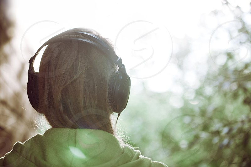 Vintage photo of a woman in headphones listening to music outdoor against bright sunlight. Instagram style color toned photo