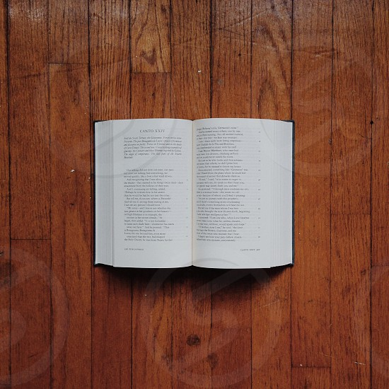 white open book page on brown wooden floor photo