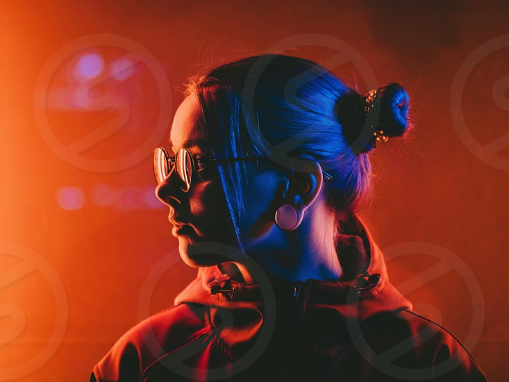 Young pretty girl with unusual hairstyle near glowing turquoise neon light of the city at night. Dyed blue hair in braids. Pensive hipster teenager in glasses. photo