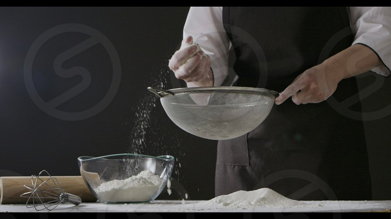 Professional chief sieves flour with sifter on a dark wooden table on a black background. Rolling pin and whisk on a table. Slow motion Full HD video 240fps 1080p. Step by step dough preparation. photo