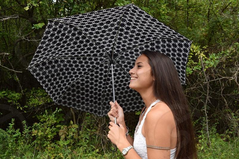 woman wearing white halter top holding black umbrella walking beside the green grasses photo