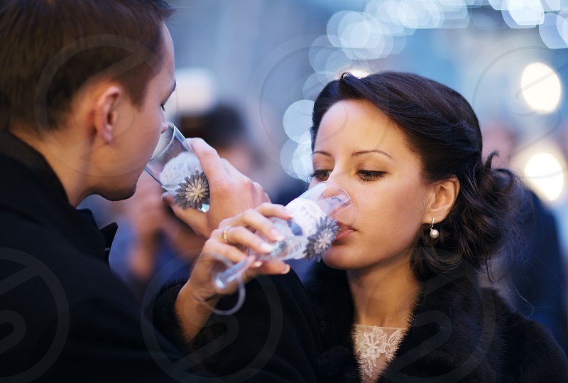 Couple toasting each other with champagne entwining their arms in a symbolic gesture of love and commitment as they sip from their glasses photo
