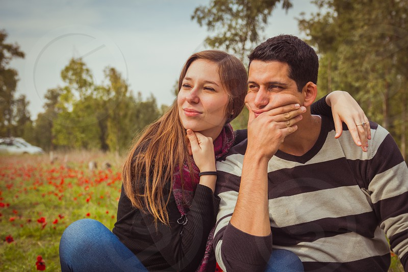 Young couple looking away with a thoughtful look while sitting on the grass in a field of red poppies. photo