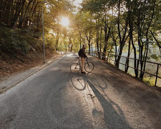 man riding a bike on black asphalt road near gray street light during daytime photo